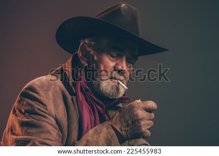 Old rough western cowboy with gray beard and brown hat lighting a cigarette. Low key studio shot. - stock photo