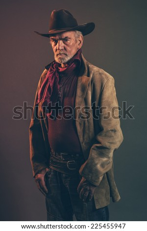 Old rough western cowboy with gray beard and brown hat. Low key studio shot. - stock photo