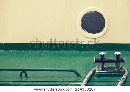 Old round porthole in gray ship hull and black mooring bollard on green deck, vintage toned photo with old style filter effect - stock photo