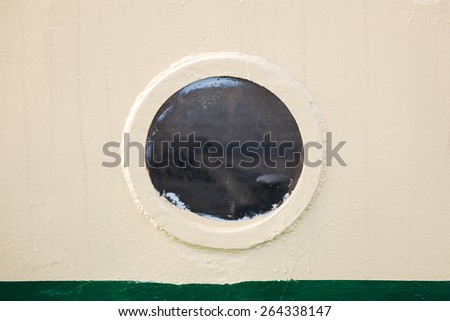 Old round porthole in gray ship hull, vintage toned photo with old style filter effect - stock photo