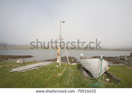 Old rowboat at coast in Iceland - stock photo