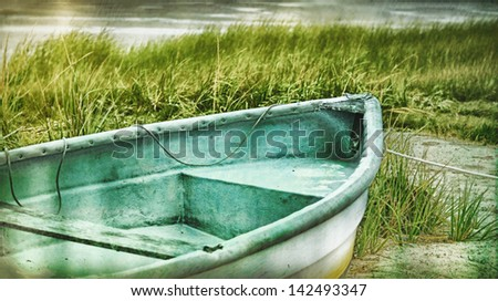 Old rowboat on the beach in the dune grasses, Bass River,  Cape Cod Massachusetts, USA. Vintage retro feel. - stock photo