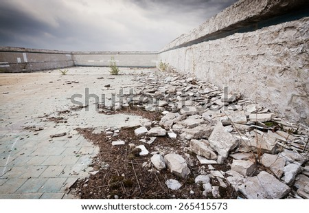 Old ruined abandoned swimming pool with dramatic sky - stock photo