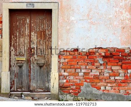 Old ruined door in brick wall background - stock photo