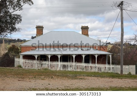 Old run down Australian house with corrugated iron roof, verandah with fancywork and  white picket fence in rural countryside scene.  A bygone era. - stock photo