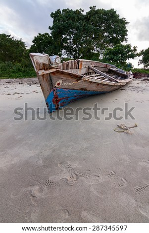 old run down dhow traditional sailing vessel moored on a beach for repairing or for scrap - stock photo