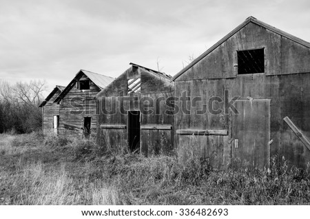 Old rundown rustic farm sheds side by side in black & white - stock photo