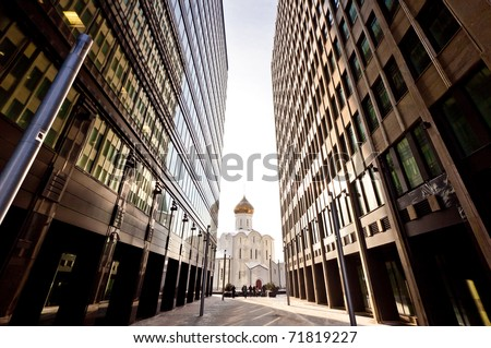 Old russian church between two modern skyscrapers. May be used as contrasts concept. - stock photo