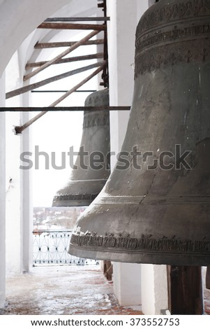 Old Russian church. Closeup of big ancient bronze bells on belfry - stock photo