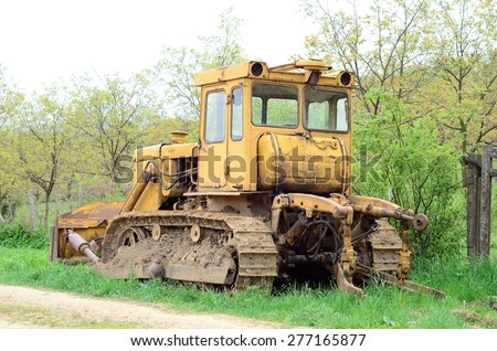 Old Russian-made crawler parking on the grass (back view) - stock photo