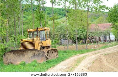 Old Russian-made crawler parking on the grass, farmhouse in the background - stock photo