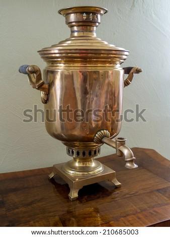 Old Russian tea brewing samovar standing on wooden tea table - stock photo