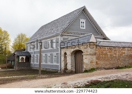 old Russian wooden house and outbuildings behind a stone fence - stock photo
