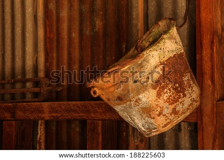 Old rusted bucket hangs against a tin wall inside an abandoned metal shed/Closeup of Vintage Rusted Bucket hanging on Inside Metal Wall of Old Shed/Rusted pail hangs in vintage metal shed - stock photo