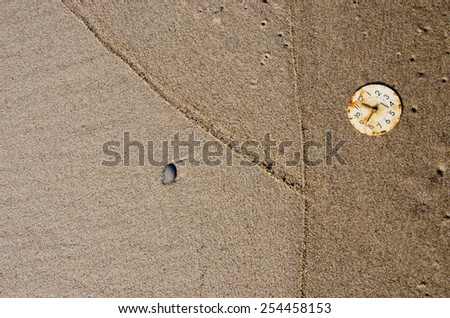 old rusted clock-face on wet sea beach sand. Time concept - stock photo