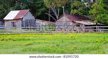 Old, rusted horse barn and shed in Georgia. - stock photo