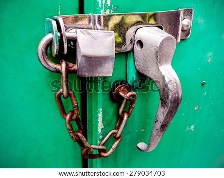 Old rusted lock on a  green door / Old rusted lock / Old rusted lock on a green door (lock, rust, security) - stock photo