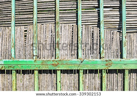 Old rusted metal decorative grate with dry cane fence behind him. Retro style, classical decor, unusual texture. - stock photo