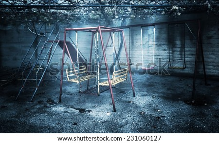 Old rusted playground, abandoned aged swings, destroyed childhood, damages in attraction park, war and poverty concept - stock photo