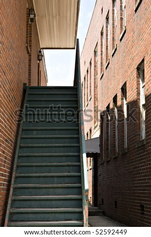 Old rusted staircase to brick building by alley - stock photo