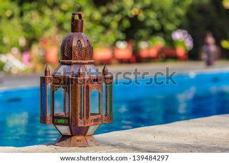 Old rustic lamp standing next to the swimming pool - stock photo