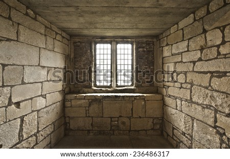 Old rustic looking midieval window cell with bricks - stock photo