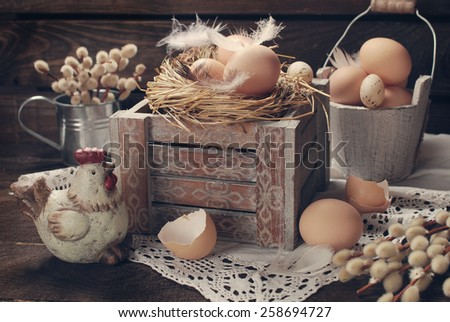 old rustic still life with eggs in nest on vintage wooden box for easter - stock photo