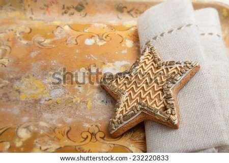 Old, rustic tray with frosted star shaped cookie against folded linen napkin. Backlit detail with shallow depth of field. - stock photo