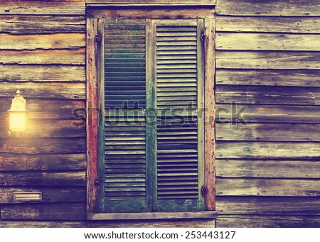 Old rustic vintage antique dilapidated run down leaning house home building structure with green closed shut shutters over window and porch light lantern glowing turned on  - stock photo
