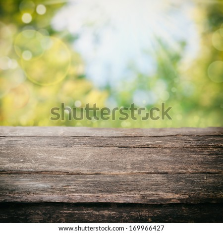 Old rustic weathered wooden table in a country kitchen under a white cottage pane window letting in bright fresh daylight, space for product placement - stock photo