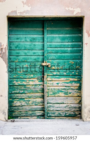 Old rustic wooden doors painted in green - stock photo