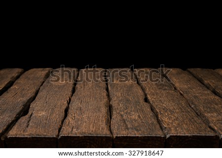 Old rustic wooden table top with solid black background. - stock photo