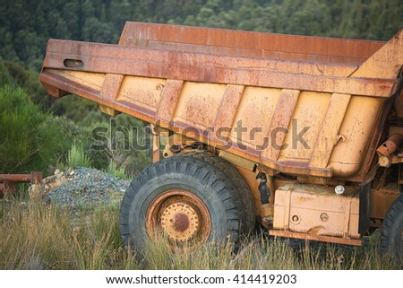 Old rusty abandoned Mining Dump Truck in a field - stock photo