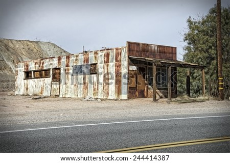 Old rusty abandoned warehouse made with metal sheets - stock photo
