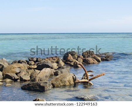Old rusty anchor on the beach of Red Sea. Egypt - stock photo