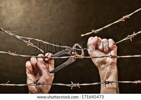 old rusty barbed wire with hand - stock photo