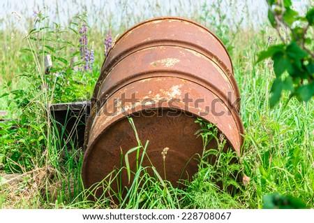 Old rusty barrel on gras  - stock photo