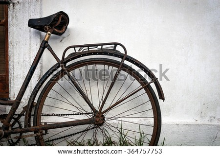 Old Rusty Bicycle leaning against a white house wall - stock photo