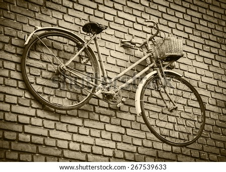 Old rusty bike attached to red brick wall. Aged photo. Sepia. Vignette. - stock photo