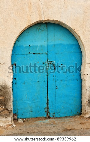Old rusty blue door of so typical shape for Tunisia - stock photo