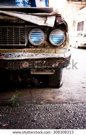 Old rusty car headlight - stock photo