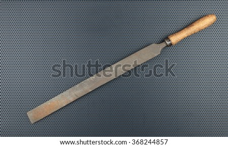 Old rusty file rasp on a metallic background - stock photo
