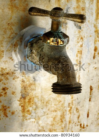 Old rusty garden faucet on wall of home or shed - stock photo