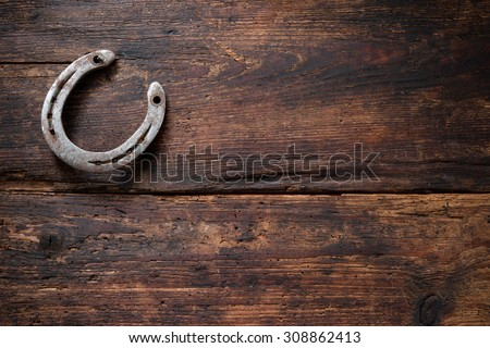 Old rusty horseshoe on vintage wooden board - stock photo