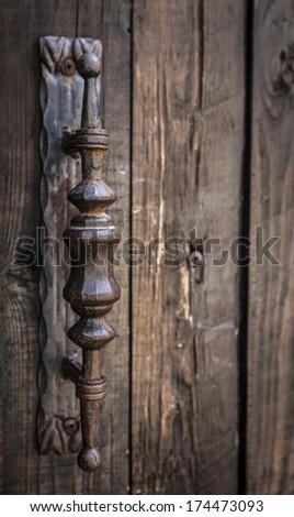 Old rusty  iron door handle mounted on old wood door - stock photo