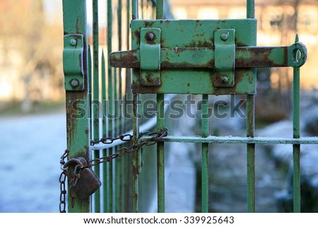 Old rusty iron gate with locking bar and padlock with chain - stock photo