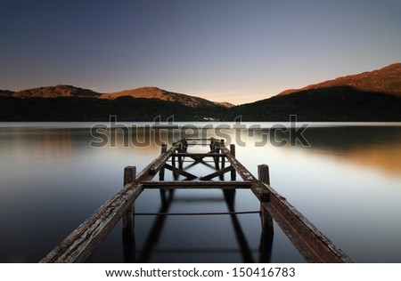 Old, rusty jetty at Sunset by Loch Lomond, Loch Lomond and The Trossachs National Park, Scotland - stock photo