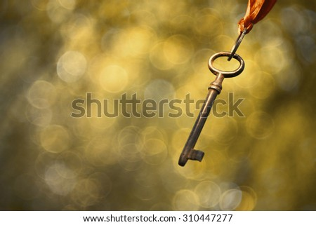 Old rusty key hanging in the air - stock photo