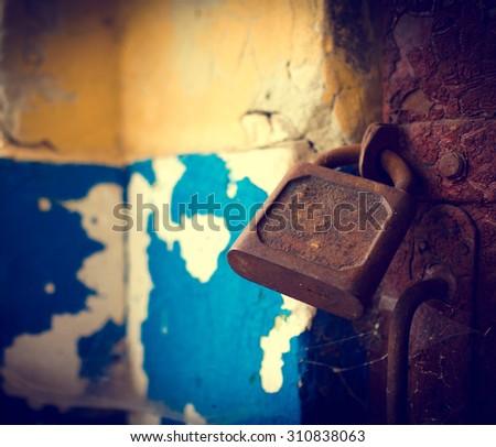 Old rusty lock on the vintage rural wooden door - stock photo