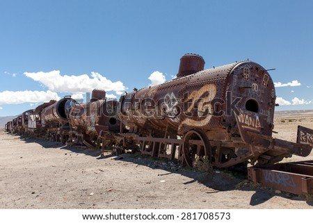Old rusty locomotive.Uyuni, train cemetery, Bolivia. Blue sky background with white clouds - stock photo